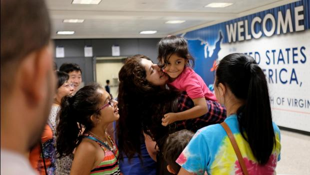 Sana Tahir holds Malaika Noman, 3, as the child enters the U.S. after a judge ruled that President Trump's temporary ban on travelers from six Muslim-majority countries cannot stop grandparents and other relatives of U.S. citizens from entering.