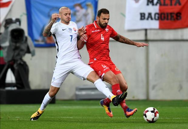 Slovakia's Vladimir Weiss in action with Malta's Steve Borg.