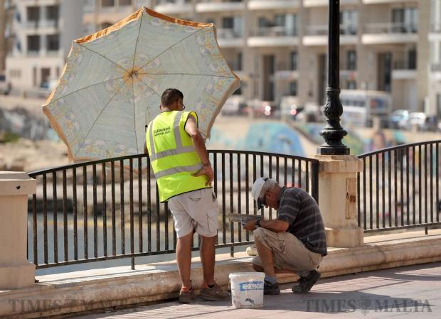 A worker paints the Sliema Front promenade while another holds an umbrella on July 13. Photo: Chris Sant Fournier