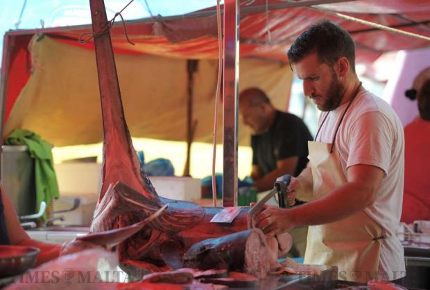 A fish monger slices a piece of swordfish at the Fish Festival in Marsaxlokk on September 12. Photo: Matthew Mirabelli