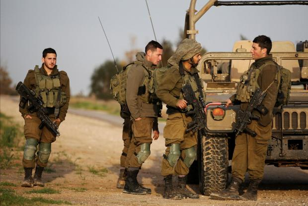 Israeli soldiers stands near a military jeep next to the border fence with the southern Gaza Strip.