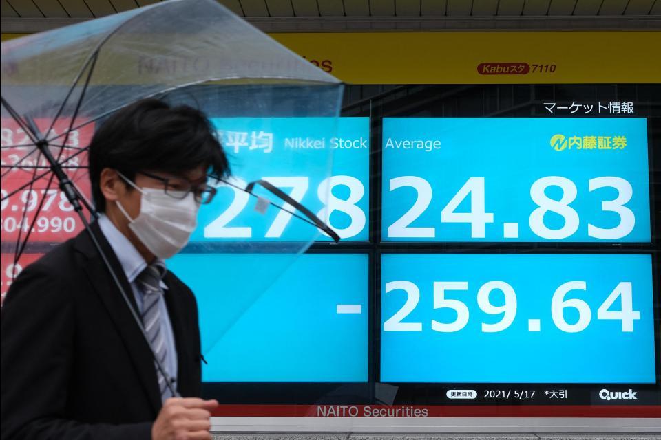A man walks past a Tokyo Stock Exchange electronic quotation board. Photo: Kazuhiro Nogi / AFP