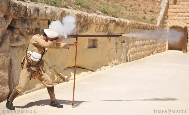 An actor ducks as he fires a musket during a re-enactment at Fort Rinella on June 12. More then 300 schoolchildren will take part in the 'Hands on Heritage Programme' during the summer, which will allow them to handle tools and weapons from different eras, try out armour and equipment and walk in the footsteps of the military. Photo: Chris Sant Fournier