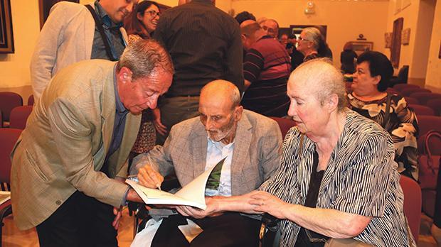 Joe Sultana signing a publication, helped by his wife. Photo: Charles Spiteri