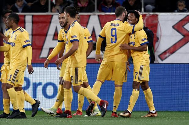 Juan Cuadrado is mobbed by his Juventus team-mates after scoring at Olympiakos.