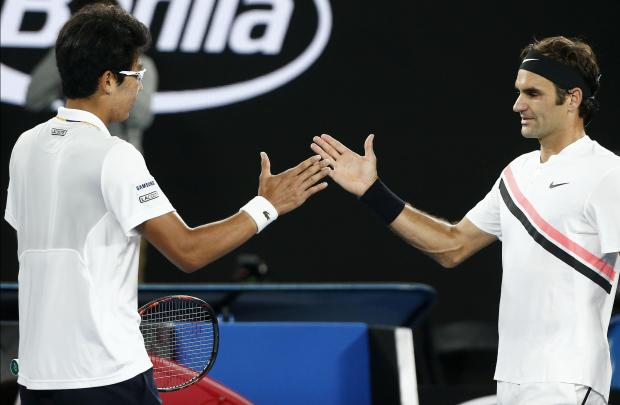 Chung Hyeon of South Korea shakes hands with Roger Federer of Switzerland after Chung retired from their match.