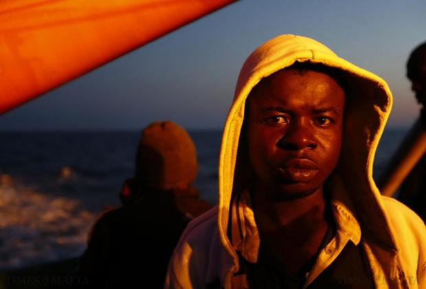 A migrant stands on the deck of the Medecins san Frontiere (MSF) ship Bourbon Argos off the coast of Libya at dusk on August 7. The 241 mostly West African migrants on the ship were taken to Trapani in Sicily. Photo: Darrin Zammit Lupi