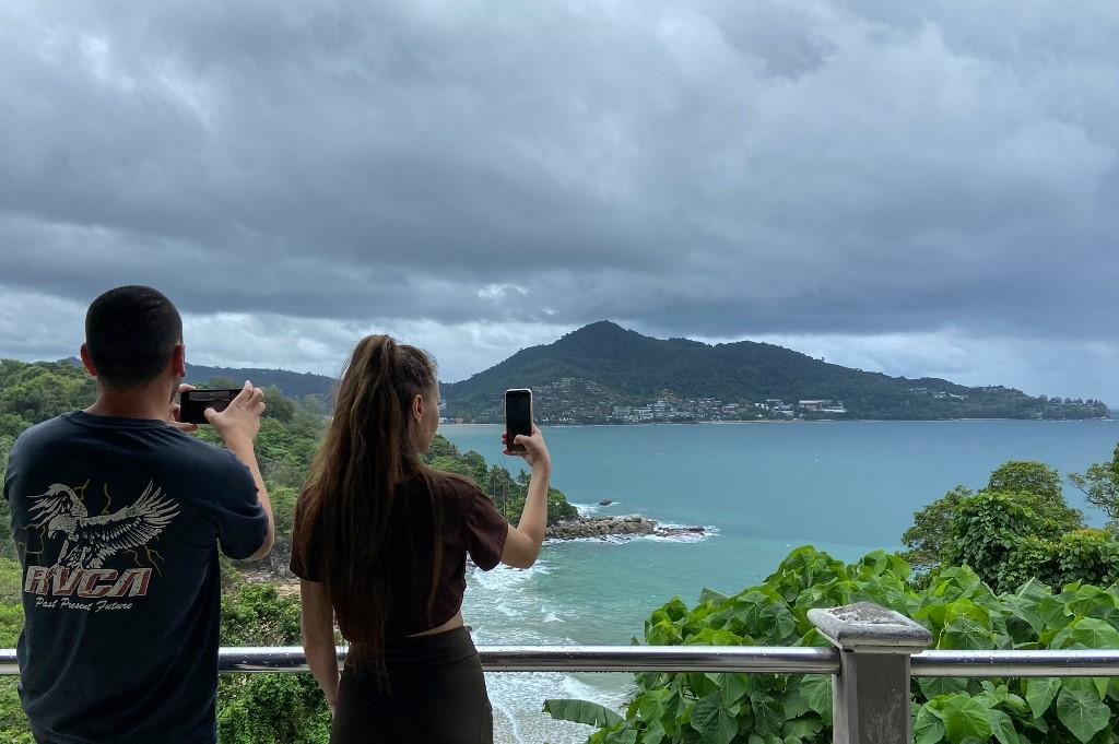 Tourists using their mobile phones to take pictures of the view from Laem Sing viewpoint in Phuket.