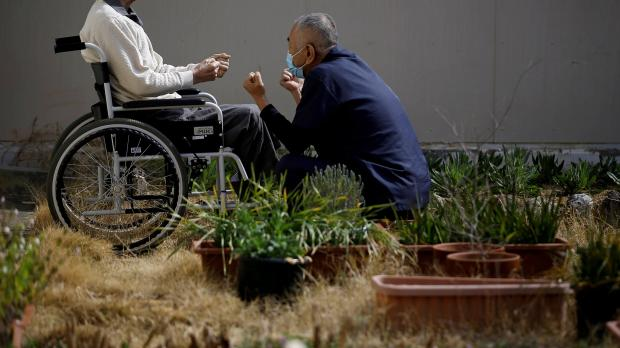 A 92-year-old man in a wheel chair, imprisoned for life in the Tokushima prison, for murder, rape and other offences, exercises with a care worker in a courtyard at the Tokushima prison in Tokushima, Japan, 2018. REUTERS
