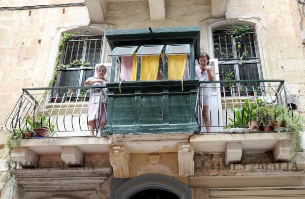 Two women stand on a Valletta balcony on September 6. Photo: Chris Sant Fournier