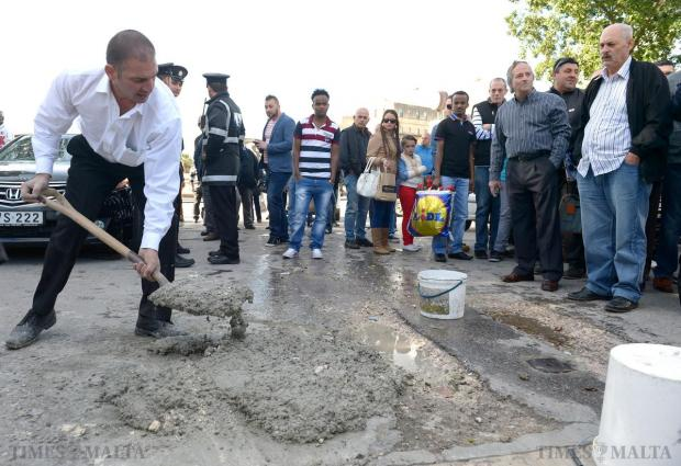 Ivan John Grima Hammett fills two holes with cement at City Gate, Valletta on December 8, whilst being urged on by the general public after police failed to stop him. Photo: Matthew Mirabelli