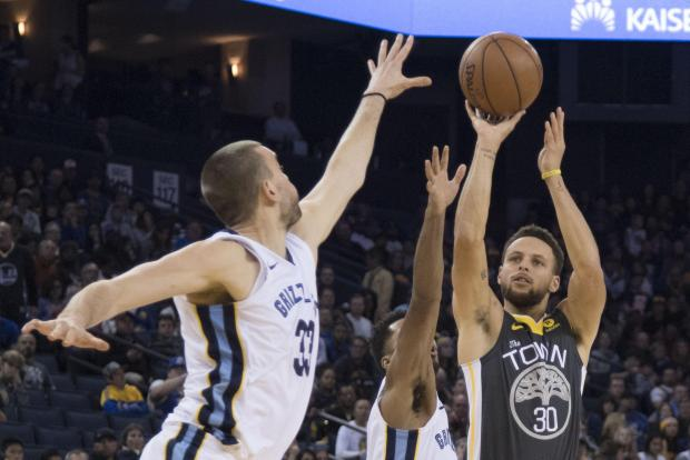 Golden State Warriors guard Stephen Curry (30) shoots the basketball against Memphis Grizzlies center Marc Gasol (33) and guard Andrew Harrison (5) during the third quarter at Oracle Arena.