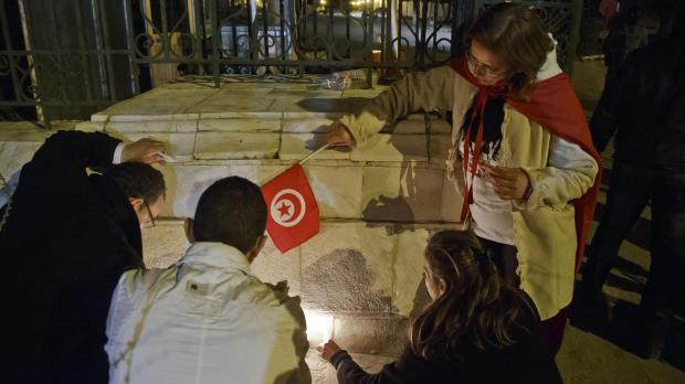 Tunisians light candles at the entrance gate of the National Bardo Museum where scores of people were killed after gunmen staged an attack. Photo: Michel Euler, PA