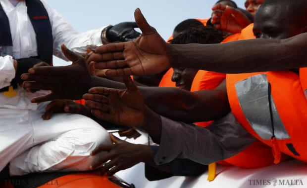 Migrants reach out to grab hold of Migrant Offshore Aid Station (MOAS) rescuers on a RHIB (Rigid-hulled inflatable boat) before being taken to the MOAS ship MV Phoenix some 32 kilometres off the coast of Libya, August 3, 2015. 118 migrants were rescued from a rubber dinghy off Libya on Monday morning. The Phoenix, manned by personnel from international non-governmental organisations Medecins san Frontiere (MSF) and MOAS, is the first privately funded vessel to operate in the Mediterranean. Photo: Darrin Zammit Lupi