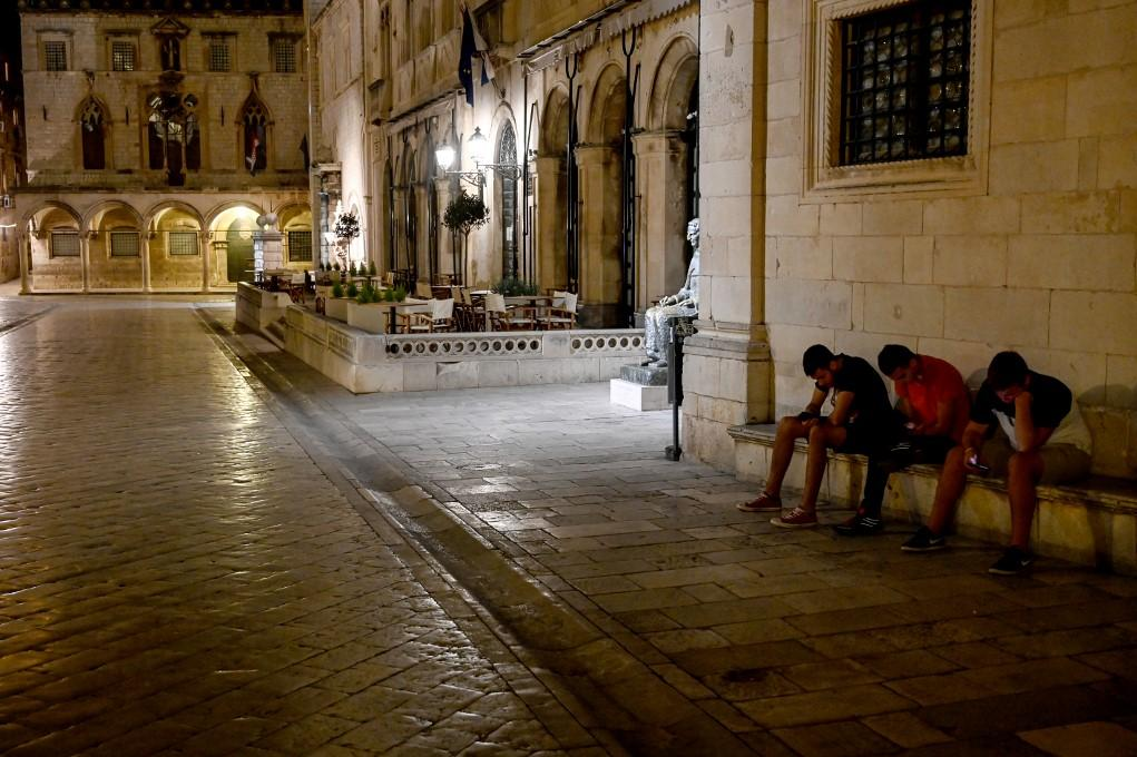 Three youths look at their mobile phones as they sit in an empty street in Dubrovnik. Photo: AFP