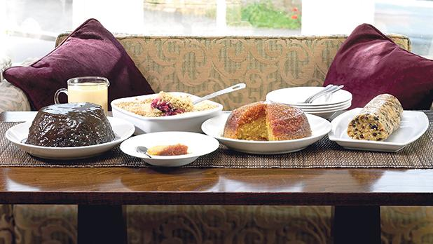 A buffet of Pudding Club puddings – sticky toffee and date pudding, apple and blackberry crumble, syrup sponge and Spotted Dick, all with custard.