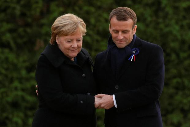 French President Emmanuel Macron and German Chancellor Angela Merkel hold hands after unveiling a plaque in the Clairiere of Rethondes. Photo: Reuters