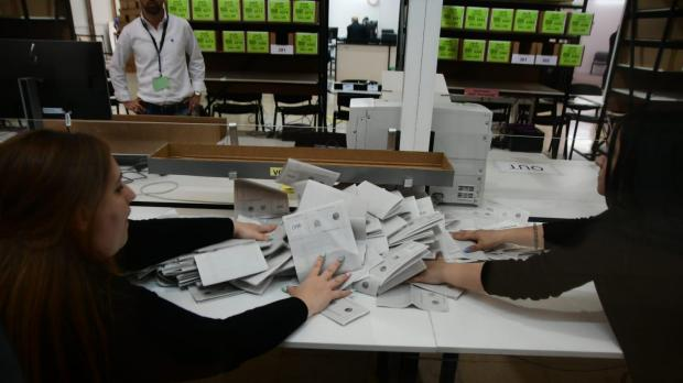 Ballot papers are taken out of ballot boxes.
