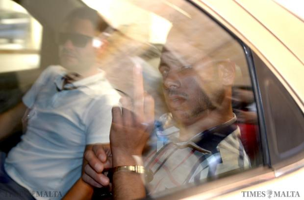 Libyan national, Ehab Zorgani reacts defiantly to photographers waiting for him as he arrives in court in Valletta to face charges of knifing six men on September 15. Photo: Matthew Mirabelli