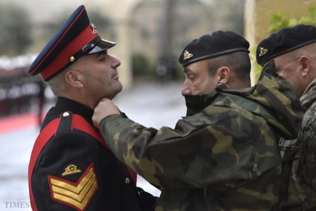 An Armed Forces of Malta soldier arranges a colleague's collar shortly before Queen Elizabeth's arrival at San Anton Palace in Attard on November 26. Photo: Mark Zammit Cordina