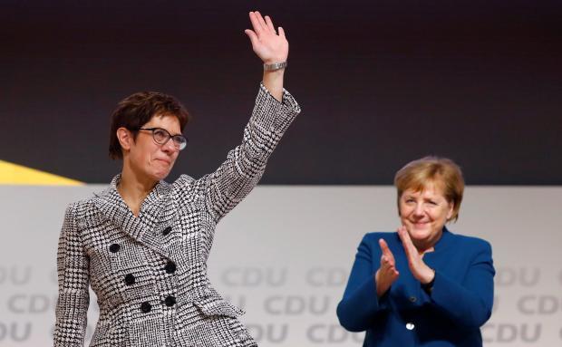 Annegret Kramp-Karrenbauer waves next to German Chancellor Angela Merkel.