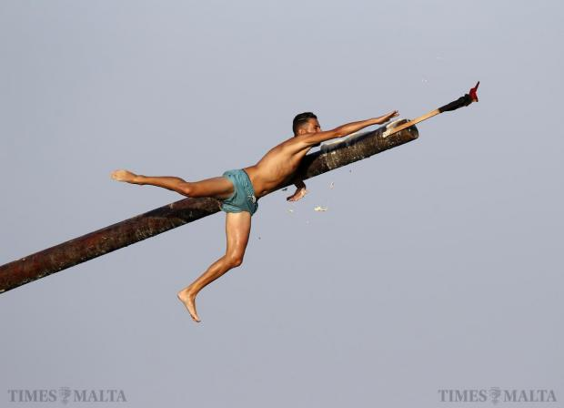 "A man tries to grab a flag as he slips off the ""gostra"", a pole covered in grease, during the week-long celebrations for the religious feast of St Julian, patron of the town of St Julian's, on August 24. Photo: Darrin Zammit Lupi"