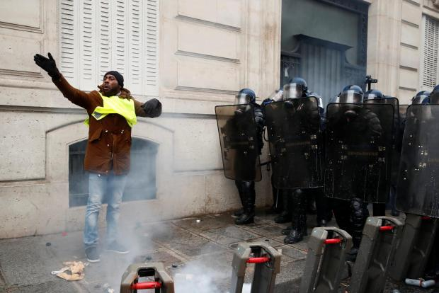 "Tear gas floats in the air around French gendarmes who secure a street during a national day of protest by the ""yellow vests"" movement in Paris. Photo: Reuters"