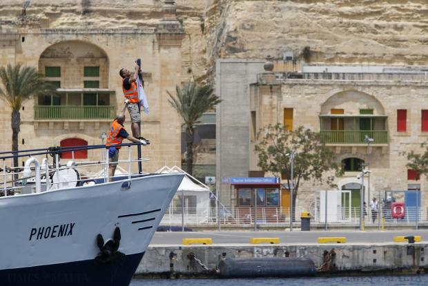 Migrant Offshore Aid Station (MOAS) crew members arrange a flag on board the ship MV Phoenix as it sails out of Valletta's Grand Harbour on May 2. The 40-metre ship MV Phoenix, manned by personnel from international non-governmental organisations Medecins san Frontiere (MSF) and MOAS, left Malta for a six-month mission to search for and rescue migrants in the Mediterranean. The Phoenix is the first privately funded vessel to operate in the Mediterranean. Photo: Darrin Zammit Lupi