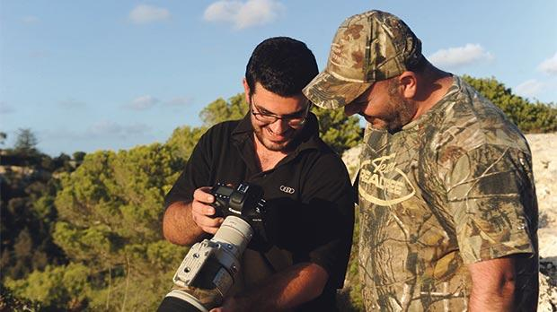 Bird photographer Matthew Scerri and hunter Kevin Holmes look at pictures. Photo: Steve Zammit Lupi