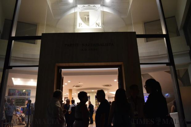 Nationalist Party supporters are shadowed whilst the emblem made from glass on top of the main entrance to the Dar Centrali is lit up on September 02. Photo: Mark Zammit Cordina