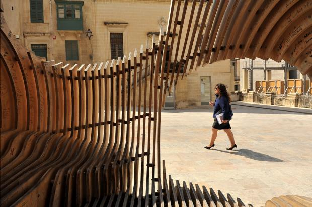 A woman walks past a wooden sculpture in Valletta on March 16. Photo: Chris Sant Founier