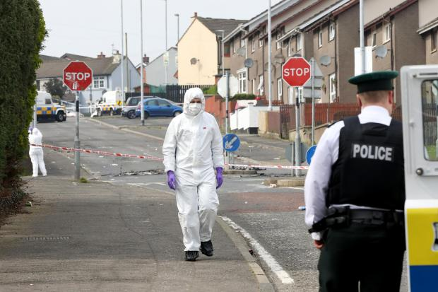 Police forensic experts inspect the scene where a journalist was fatally shot.