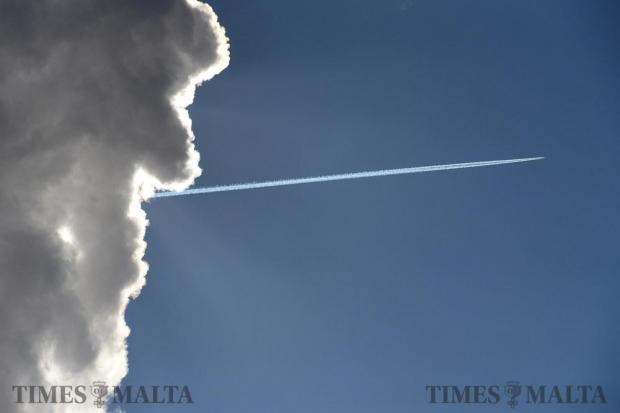 An aircraft flies above a cloud as seen from Valletta on February 12. Photo: Matthew Mirabelli
