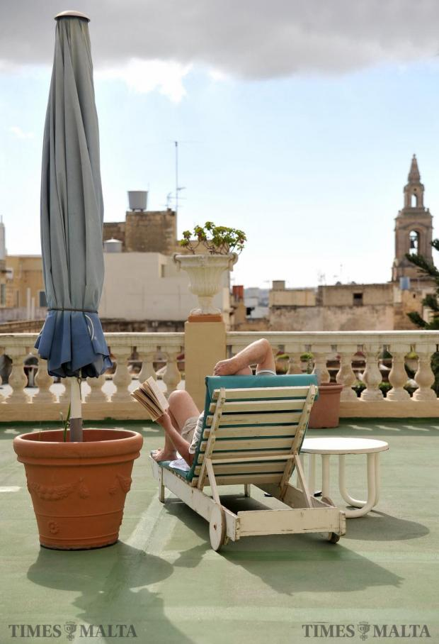 A tourist relaxes on the terrace of the Imperial Hotel a day before it closes it's doors after over 150 years of history on February 8. Photo: Chris Sant Fournier