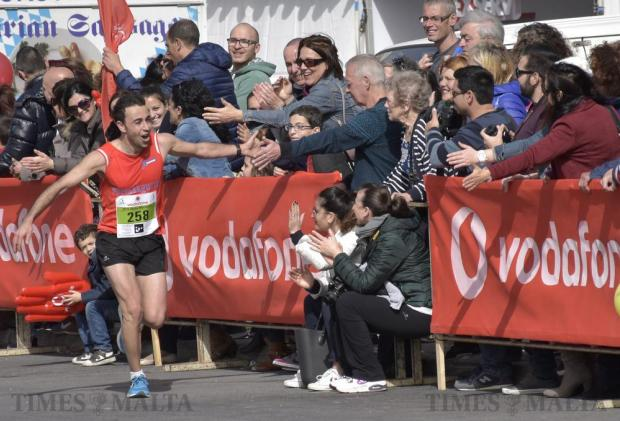 A participant high-fives spectators close to the finish line of the Malta Marathon in Sliema on 28 February. Photo: Mark Zammit Cordina