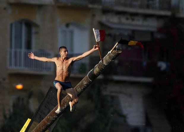 "A man grabs a flag as he slips off the ""gostra"", a pole covered in grease, during the week-long celebrations for the religious feast of St Julian, patron of the town of St Julian's, on August 24. Photo: Darrin Zammit Lupi"