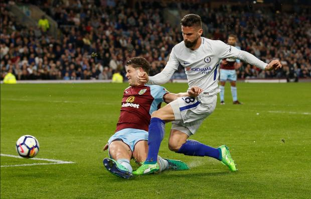 Chelsea's Olivier Giroud shoots at goal under pressure from Burnley's James Tarkowski.