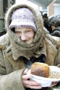 A woman holds a plate of food she received at a distribution point for homeless people at a train station in Moscow, yesterday.