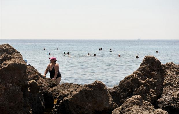 A woman climbs out of the sea after a swim at Ghar Lapsi on July 19. Photo: Chris Sant Fournier