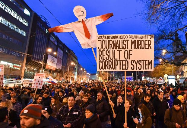 "Protesters holds placards during a rally under the slogan ""For a Decent Slovakia"", against corruption and to pay tribute to murdered Slovak journalist Jan Kuciak and his fiancee Martina."