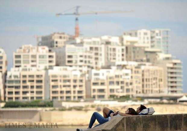 A couple lies on the Valletta bastions overlooking Marsamxett Harbour on October 5. Photo: Chris Sant Fournier