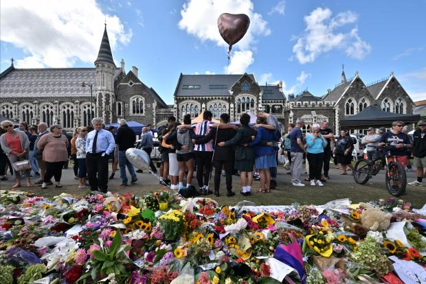 A group of students sings in front of flowers left in tribute to victims at the Botanical Garden in Christchurch. Photo: AFP