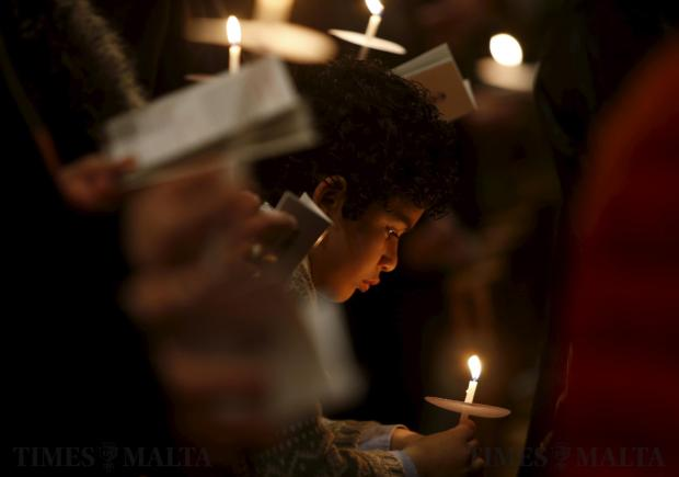 A boy holds a candle during an Easter vigil mass at St John's Co-Cathedral in Valletta on March 26. Photo: Darrin Zammit Lupi