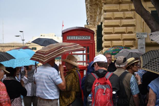 Tourists cover a traditional English phone booth with different coloured umbrellas in Republic Street Valletta. Photo: Mark Zammit Cordina