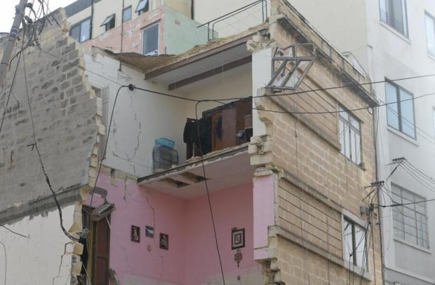The collapsed building adjacent to a construction site.