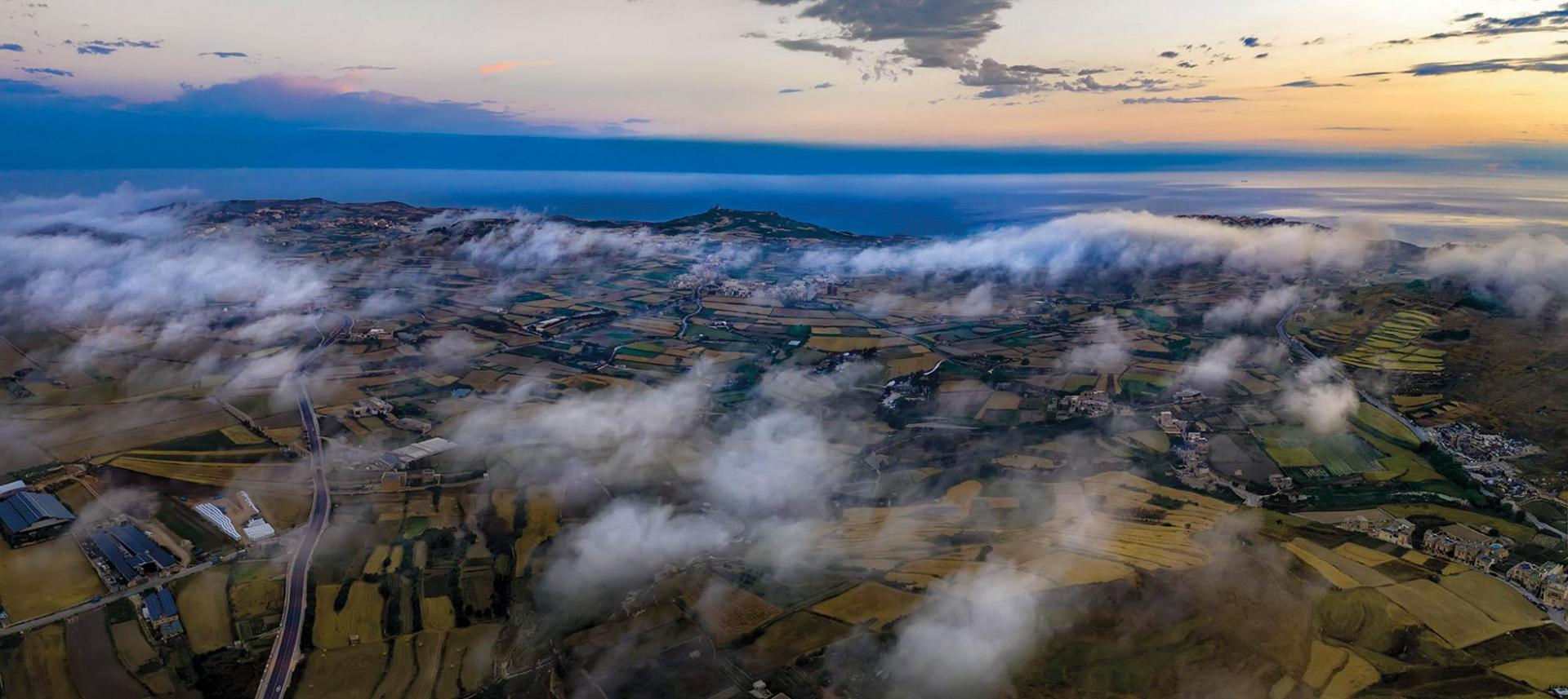 An aerial view of the west of Gozo, with the Ta' Ġordan Lighthouse visible above the low clouds.