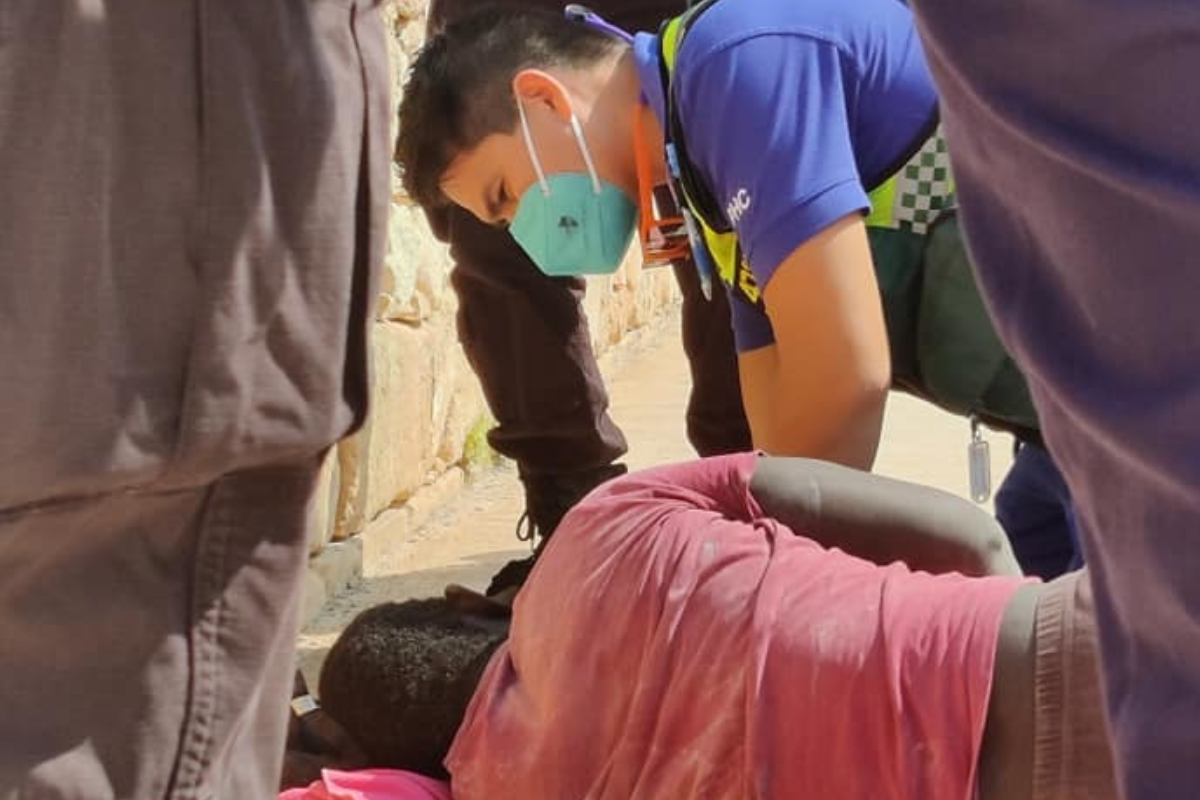 Medics treat injured Lamin Jaiteh on the side of the road. Photo: Caroline Galea