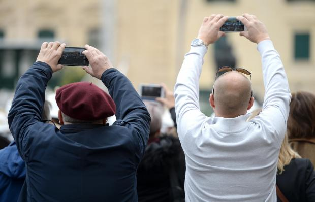 Two tourists try to take photos over a crowd at the changing of the guard St George's Square, Valletta on January 26. Photo: Matthew Mirabelli
