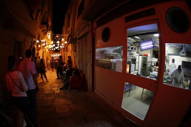 Food is prepared in a restaurant kitchen as people walk down Strait Street during Notte Bianca (White Night) celebrations in Valletta on October 3. Photo: Darrin Zammit Lupi