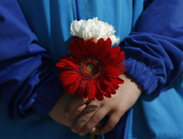 A schoolgirl from St Theresa College Primary School holds flowers during a memorial service for migrant victims in Msida on April 22. Photo: Darrin Zammit Lupi